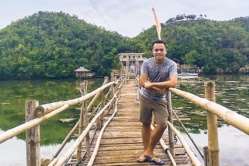 Striking a pose at the makeshift bamboo bridge in Tinagong Dagat