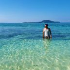 Ian Limpangog while wading the shallows of Mahaba Island with Himokilan Island in the background