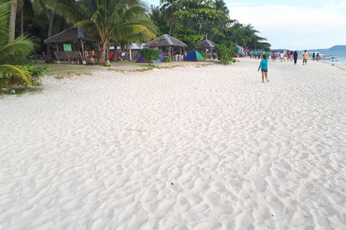 The fine and powdery white sand of Digyo Island stands out again the big crowd of campers