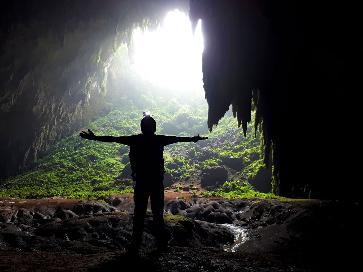 Silhouette of Ian Limpangog at the mouth of Langun Cave